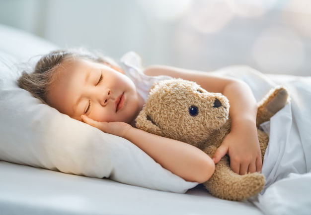 girl sleeping in bed with teddy bear